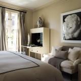 Combinatie de crem si maro inchis pentru amenajarea unui dormitor cu perdele in dungi asortate