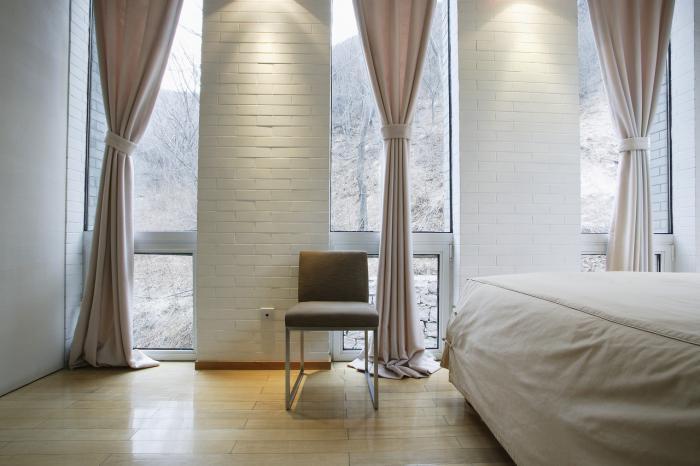 Dormitor cu perete placat cu caramida alba si fasii de draperii din bumbac crem simplu