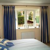 Draperii cu dungi crem si albastru electrizant pentru un dormitor mic