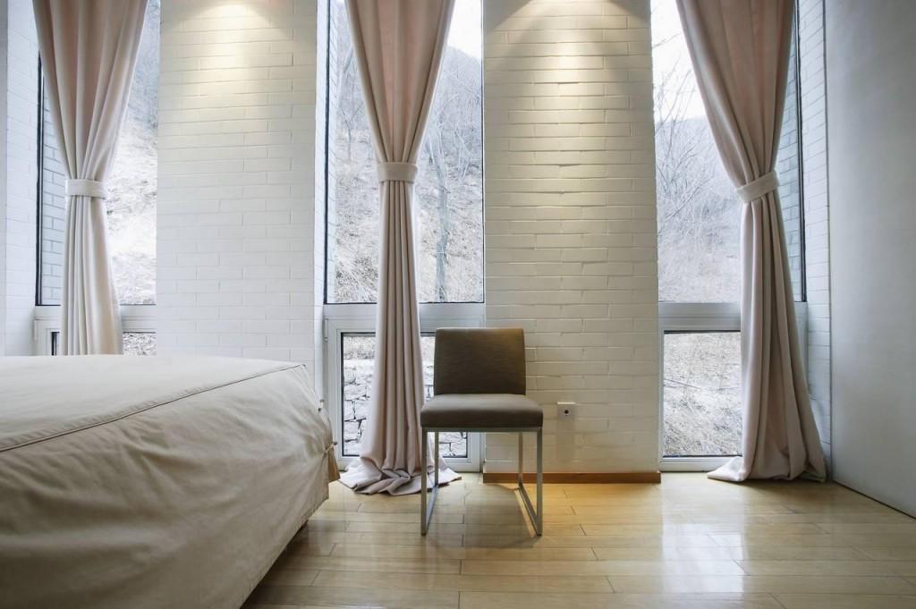 Interior de dormitor cu sistem de iluminare interesant de-a lungul zidului cu caramida alba si perdelelor din bumbac gros alb