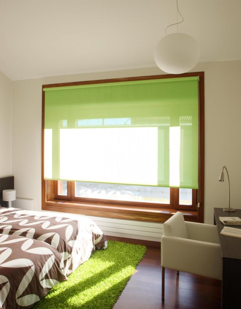 Roleta textila verde asortata cu covor verde shaggy intr-un dormitor mic cu alb si maro