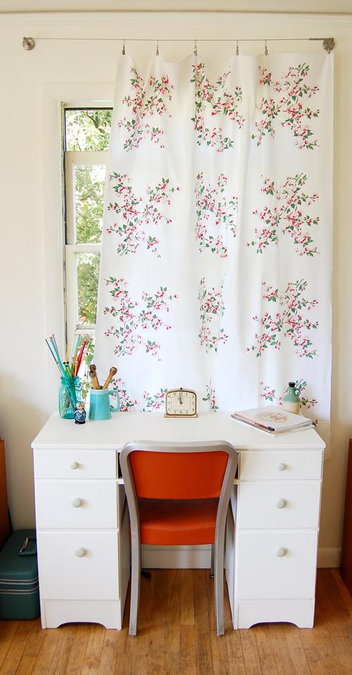 Birou mic alb cu scaun portocaliu si perdea alba simpla din bumbac cu floricele roz cu verde