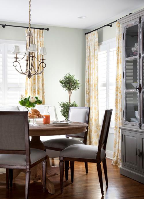 Dinning clasic traditional cu masa rotunda din lemn si ferestre cu obloane albe de interior si perdele albe cu flori galbene