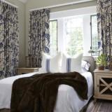 Dormitor amenajat in stil rustic cu mobilier crem si perdele alb mudar cu flori albastru aprins