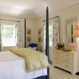 Dormitor in stil clasic cu pat pe mijloc cu baldachin si perdele albe cu motive florale abastre
