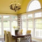 Living amenajat in stil clasic cu pereti si scaune galbene si masa din lemn masiv si perdele albe cu flori mari maro